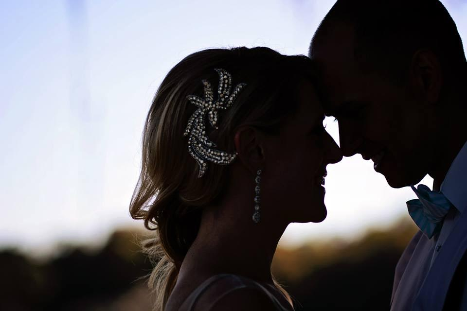 A silhouette profile photo of a bride and groom coming in for a kiss, the glint of the bride's crystal hair piece shining through the dark.