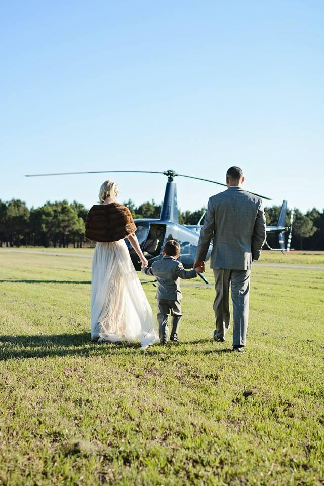 The bride, groom, and their son in his tiny tuxedo walk towards a helicopter to whisk them away for an aerial tour of Charleston and the lowcountry.