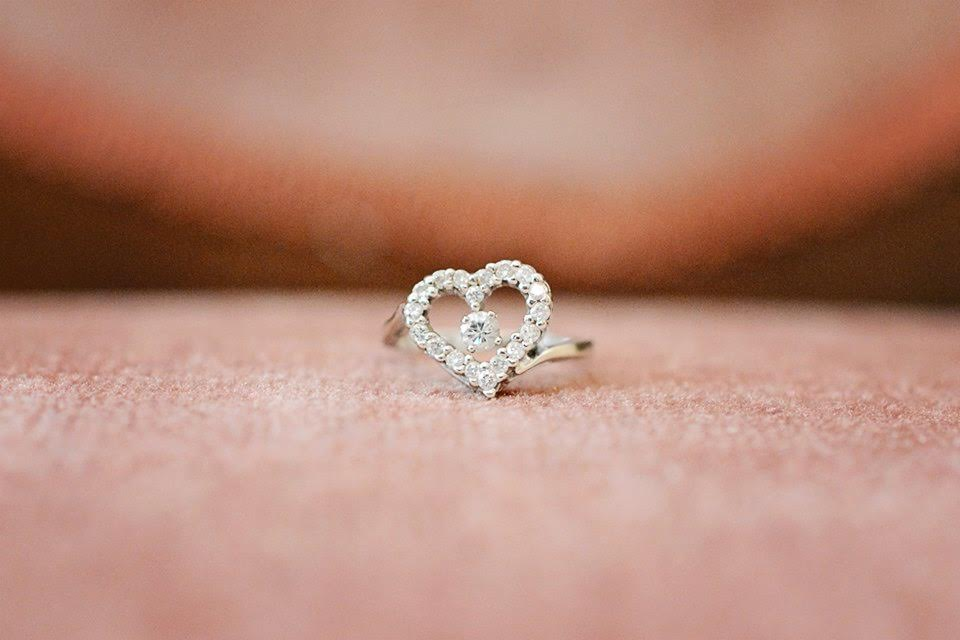 A close-up detail shot of a diamond ring in the shape of a heart.