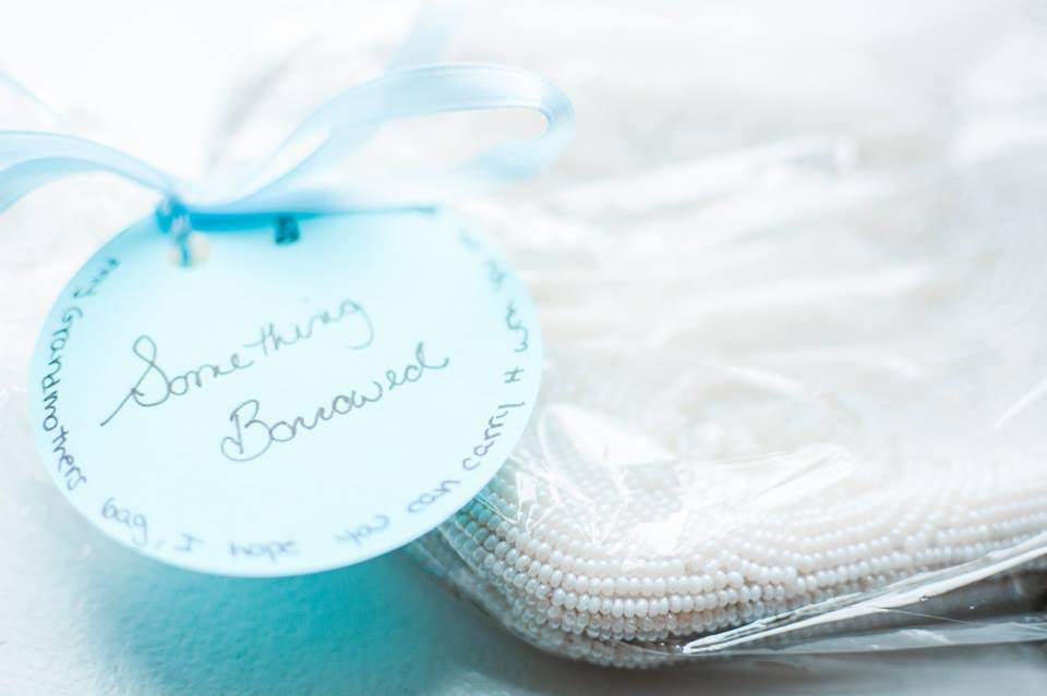 """A round blue tag with """"Something Borrowed"""" written in script adorns a white beaded handbag for a bride on her wedding day."""