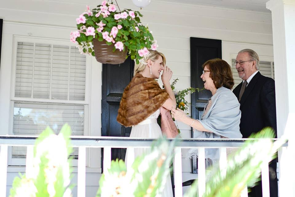 A bride, draped in a fur stole, tears up as her mom and dad walk around the corner before her surprise wedding vow renewal