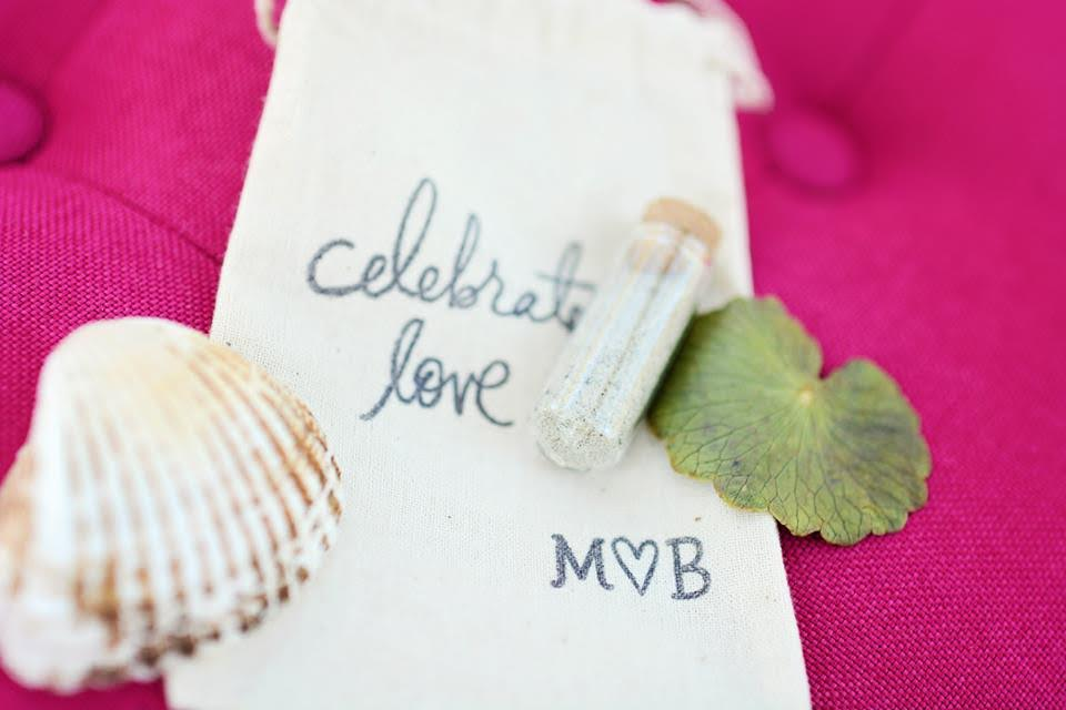 """A bag embroidered with """"celebrate love"""" lies on a fuchsia pink couch with a vial of sand and a shell to commemorate the bride and groom's beach wedding."""
