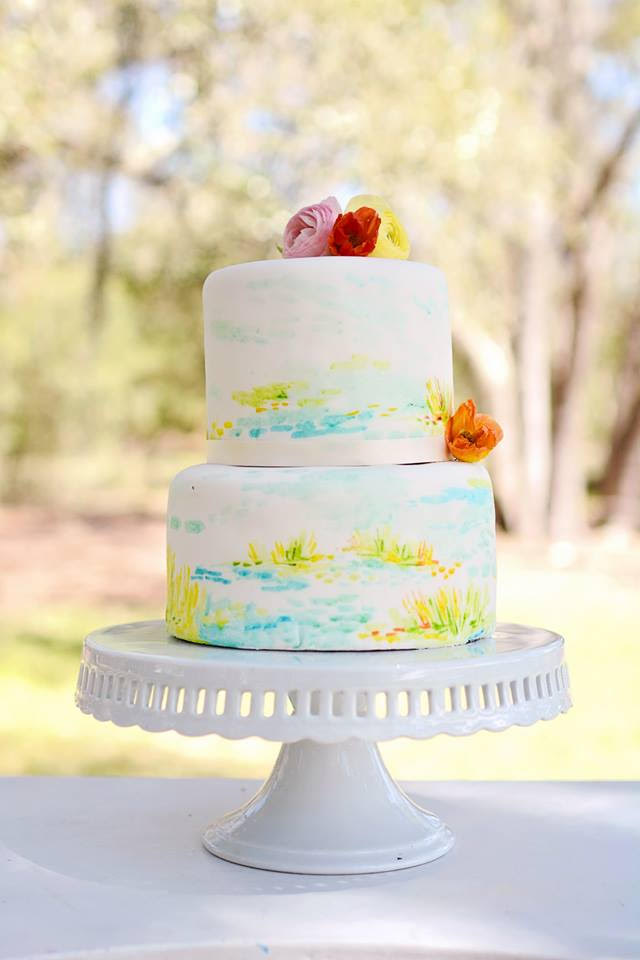 A two-tiered cake hand-painted with blue and green watercolors rests atop a milk glass cake stand.