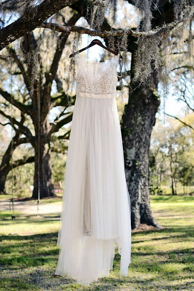 An ethereal beaded and chiffon wedding gown drifts among the branches and the moss of a grove of trees.