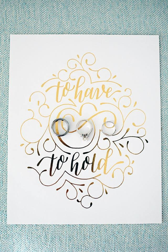 """The bride's wedding and engagement rings sit next to her groom's wedding band on top of a gold scripted card reading """"to have and to hold."""""""