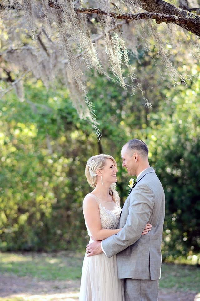 A bride and groom embrace under the Spanish moss of Charleston's sleepy oak trees.